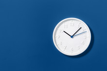 Big White Plain Classic Wall Clock On Trending Dark Blue Background. Ten O'clock. Close Up With Copy Space, Time Management Or School Concept And Summer Standard Or Winter Time Change, Opening Hours.