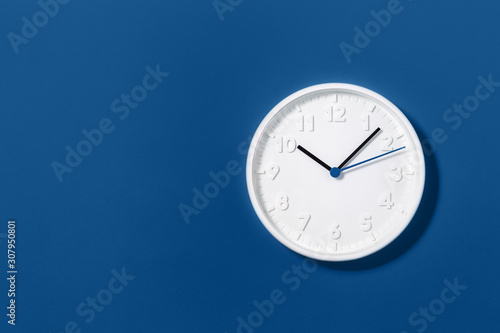 Leinwand Poster Big white plain classic wall clock on trending dark blue background