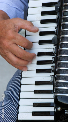 The fingers of an accordionist strike a chord on the keys of his musical instrument Canvas-taulu