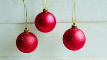 Three Red Baubles On White Wooden Background, Closeup. Merry Christmas And Happy New Year