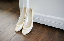 The Bride Shows White Wedding Shoes. Wedding Detail. Close Up.