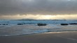 Waves gently washing and crashing across large rocks on a beach during sunrise