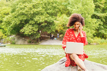 Young African American College Student With Afro Curly Hair, Wearing Red Patterned Dress, Sitting On Rocks By Lake At Central Park, New York City, Working On Laptop Computer, Talking On Cell Phone..
