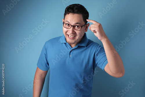Fotografia Smart Asian Man Pointing on His Head and Smile
