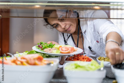 Canvastavla Medical doctor bent over with a salad plate picking up food at a self-service re