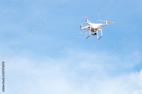 Photo White Quad Copter drone hovering and flying with bright blue sky space for copy text