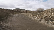 Two Men Ride On A Horse Through A Dirt Road In Patagonia.