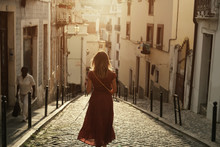 Young Traveling Woman Wearing Long Red Dress Walking On Lisbon Streets Looking At Beautiful View