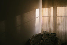 Cozy Window With Curtains In The Room. Shadow And Sunlight On The Wall. Pillow In Wicker Chair