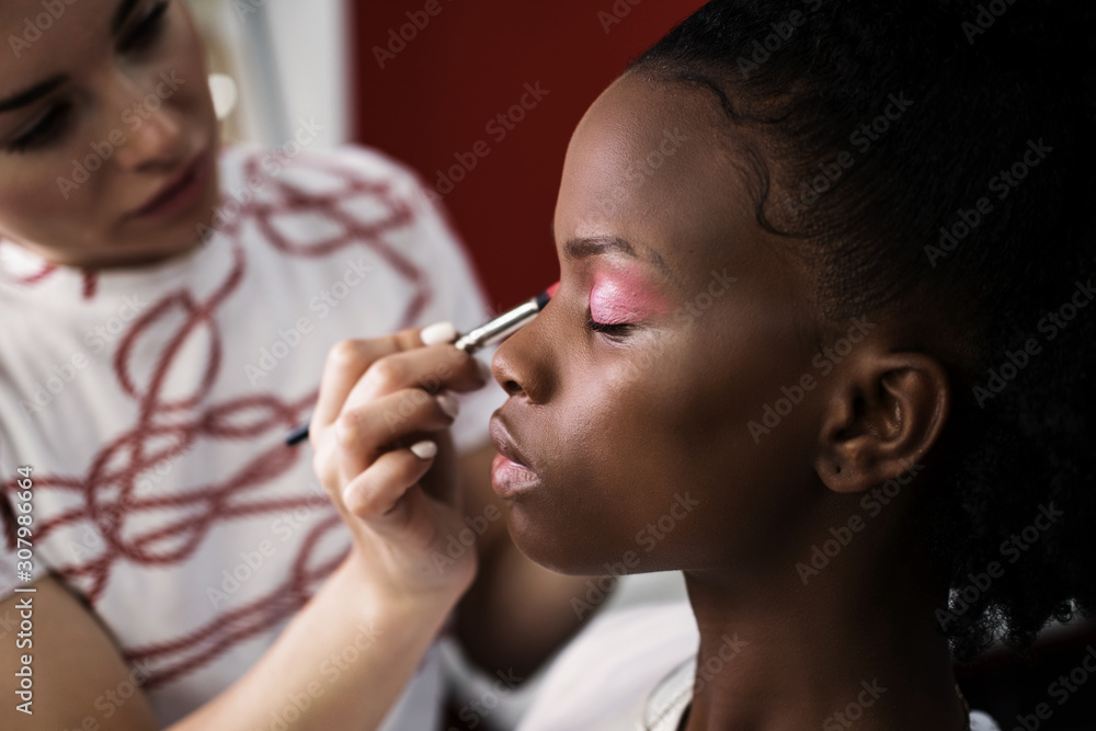 Fototapeta Make up artist doing makeup for african fashion model in studio