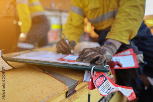 Obraz na plátne Personnel red danger locks attached with danger tags are locking on safety isola