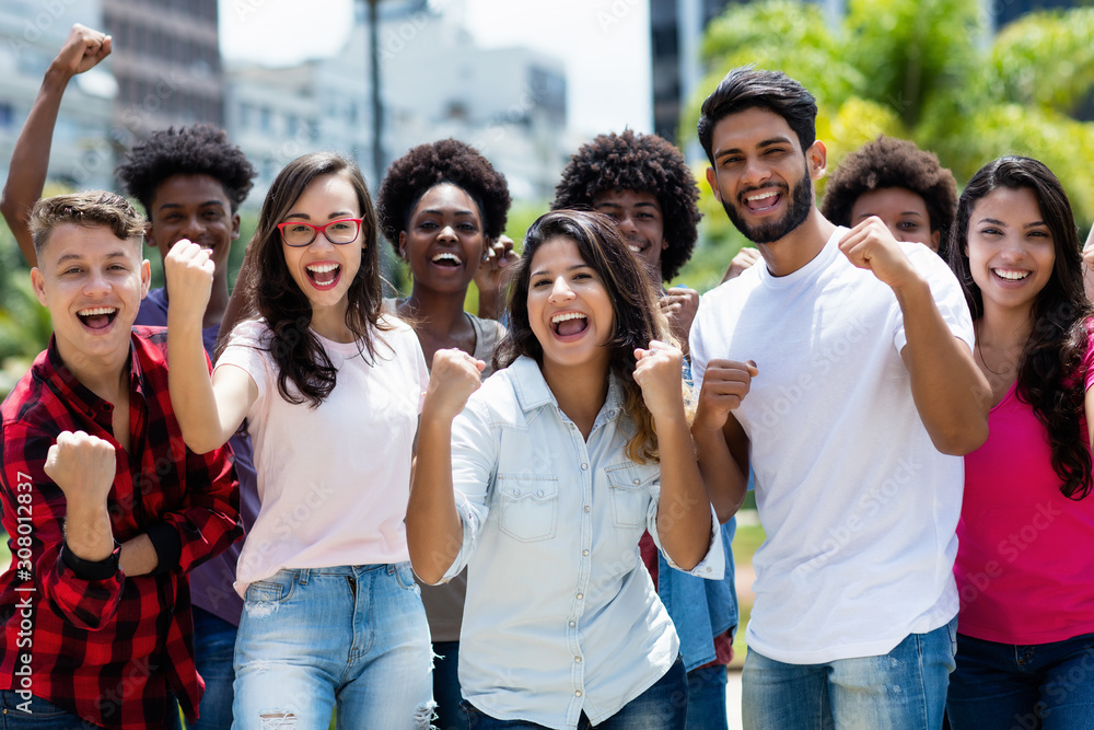 Fototapeta Group of successful cheering latin and caucasian and hispanic and african american young adults