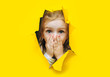 canvas print picture - A little girl with red hair looks out through a hole in torn yellow paper and covers her mouth with her hands and eyes wide in surprise. The concept of surprise, shock. Discounts, sales. Copy space.