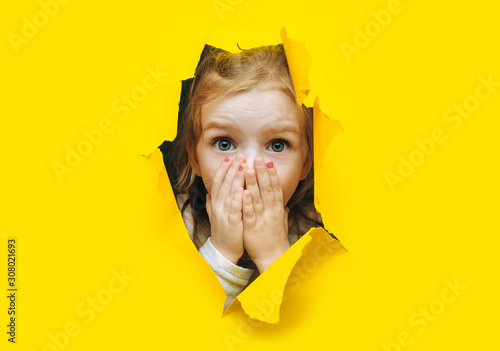 Fotografija A little girl with red hair looks out through a hole in torn yellow paper and covers her mouth with her hands and eyes wide in surprise