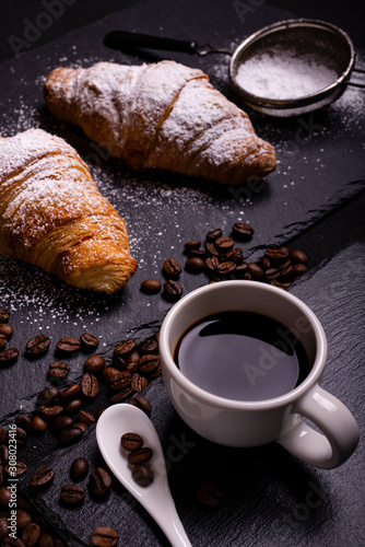 Photo cup of black coffee and croissant on a dark background