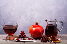 Front View, Juicy And Fresh Pomegranate, Whole And Cut With Seeds And Pomegranate Juice In A Glass Carafe