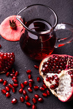 Juicy And Fresh Pomegranate, With Seeds And Pomegranate Juice In A Glass Carafe
