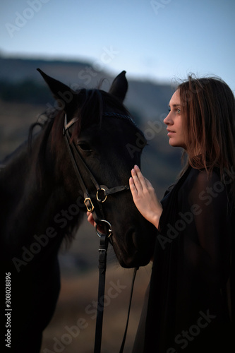 Cuadros en Lienzo Beautiful smiling young girl hugs her black horse