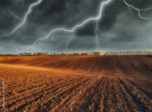 Foto auf Leinwand Schokobraun thunderstorm in the field. huge lightning over a hilly field. bad weather in the field