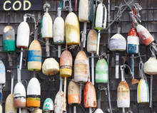 Vintage Lobster Trap Buoys Hung On Wall Of Building