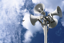 Four Loudspeakers Are Attached To A Rack Against A Background Of Clouds And A Bird.