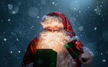 Happy Santa Claus Opening Christmas Gift Box Over Snowy Blue Background With Copy Space
