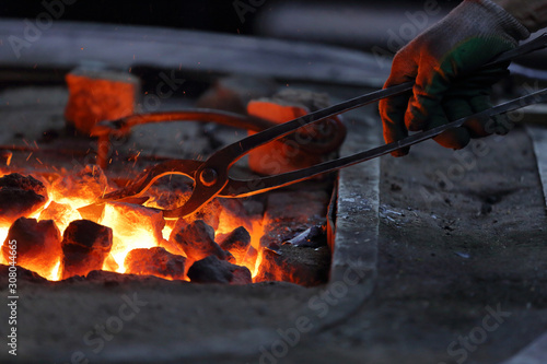 Hot coals in a furnace for heating metal for manual forging in a blacksmith work Fototapet
