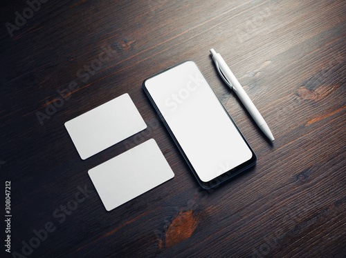 Fotografía  Photo of smartphone with blank screen, business cards and pen on wood table background