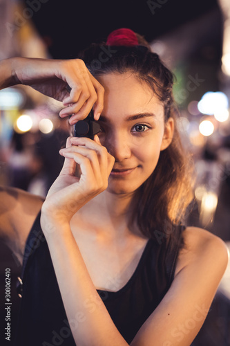 Girl holding small black cemara look pretty to pretend to take a shot, one big eye with smiling face, outdoot at night have some bokeh of light on background