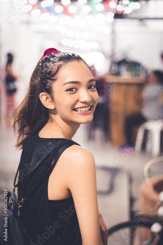 Girl turn face looking back to smile, got big eyes with smiling face, outdoot at market have some bokeh of light on background