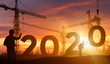 Cranes building construction 2020 year sign,Silhouette staff works as a team to prepare to welcome the new year 2020
