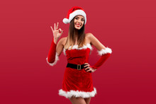 Close Up Portrait Beautifiul Caucasian Woman In Red Santa Hat On Red Studio Background. Christmas And New Year Holiday Concept.