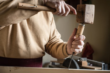 Carpenter Working With A Wooden Hammer And A Gouge