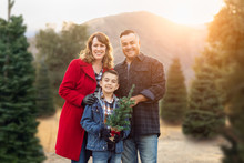 Mixed Race Family Outdoors At Christmas Tree Farm