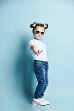 Cool Cute Little Baby Kid Girl With Funny Buns And In Sunglasses, T-shirt And Blue Jeans Is Showing V Victory Sign