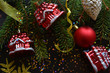 Beautiful festive Christmas composition with green spruce branches, red balls and toy houses with yellow shiny ribbons and confetti.