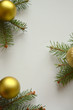 Christmas elegant vertical composition. Christmas tree branches and golden Christmas balls on a light pastel background. Christmas, New Year, winter concept. Flat lay. Copy space. Top view