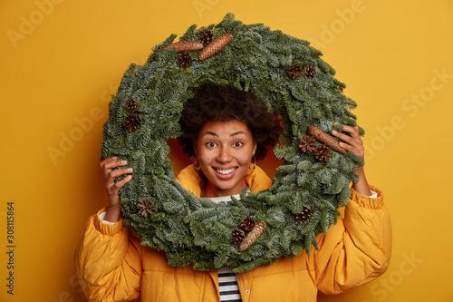 Optimistic curly woman looks through handmade Christmas wreath, being in good mood, wears down padded coat, prepares for New Year, stands against yellow background Canvas Print