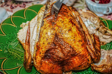 Roasted Turkey On Green Platter Being Carved - Sliced At Table For Thanksgiving Dinner - Selective Focus And Close-up.