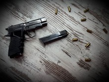 Close-up Of A Traumatic Weapon And A Magazine With Cartridges On A Wooden Surface Background