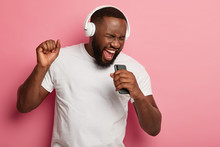 Energized Black Unshaven Man Sings To Music, Moves Actively, Wears Headphones And Casual T Shirt, Poses Against Pink Background, Keeps Mouth Widely Opened, Enjoys Life, Isolated On Pink Studio Wall
