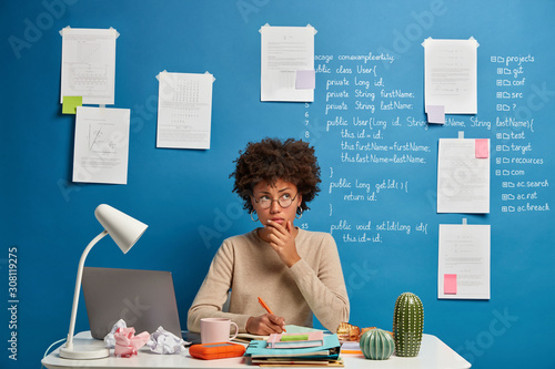 Photo Thoughtful attractive woman in spectacles writes in diary to do list of goals, m