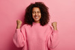 Leinwanddruck Bild - Hooray, its excellent! Overjoyed curly woman with toothy smile enjoys victory, accomplishes goal successfully, clenches fists, wears knitted sweater, celebrates triumph, isolated over pink wall