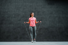 Full Length Of Fit Attractive Caucasian Sportswoman Looking Away And Preparing To Skip Skipping Rope. In Background Is Dark Wall.