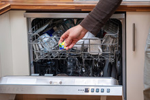 Close-up At A Hand With Washing Capsule And A Fully Loaded Dishwasher.