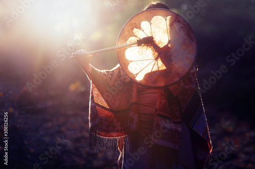 Fotografía beautiful shamanic girl playing on shaman frame drum in the nature
