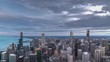 A beautiful aerial skyline panoramic sunset day to night time lapse of downtown Chicago with Lake Michigan and colorful pink and blue clouds as the sun sets and lights come on in the city.