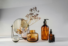 Branch Flowers In A Glass Vase, Mirror And Cosmetics Products  On White Table. Decor For Interior. Stylish Decoration For Home.