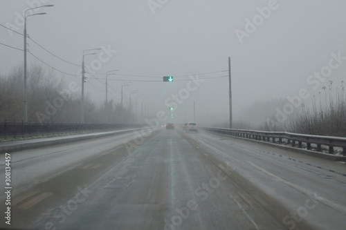 Snowy winter road during blizzard. Heavy snow storm. Wallpaper Mural