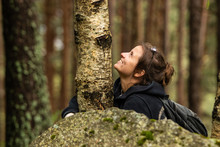 Tourist Young Woman Hugging A Tree And Smiling In The Forest During The Mountain Hike.Connecting To Nature, Protect The Environment Concept